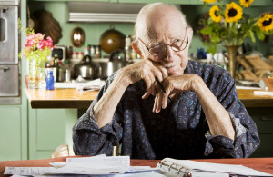 Older Man at Kitchen Table with Bills